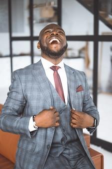 彼の人生に非常に満足しているジェスチャーは、豪華なアフロアメリカンが心から笑い、pl ...
