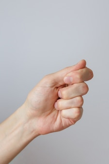 Gesture and sign, male hand holds something on a light background