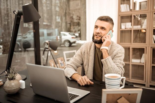 작업하는 동안 제스처. 차 한잔과 함께 노트북 앞에 앉아있는 동안 자신의 휴대 전화로 이야기하는 자영업자 사업가