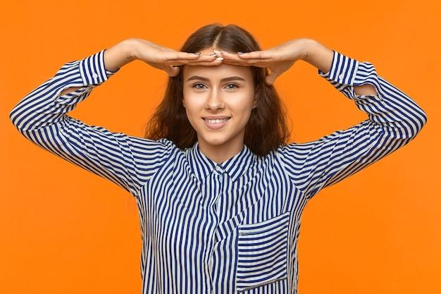 ジェスチャーとボディーランゲージ。広く笑顔のストライプのシャツで成功した幸せな希望に満ちた若い学生の女の子