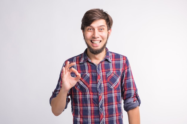 Gestures, signs and people concept - smiling confused man shows okay sign over the white background