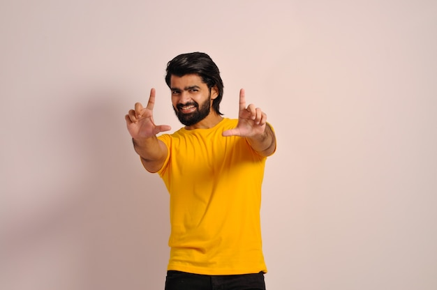Gesturing finger frame beautiful young man happy  looking at camera with gesturing finger frame
