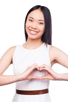 指ハートを身振りで示す。カメラを見て、白い背景に立っている間指の心を身振りで示す美しい若いアジアの女性