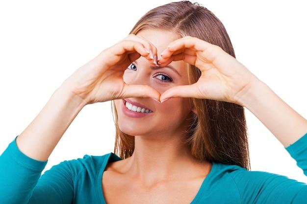 指ハートを身振りで示す。カメラを見て、白で隔離されて立っている間指の心を身振りで示す美しい若い女性