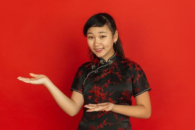 身振りで示す、ゲストを招待します。ハッピーチャイニーズニューイヤー2020。赤い背景の上のアジアの若い女の子の肖像画。伝統的な服を着た女性モデルは幸せそうに見えます。お祝い、人間の感情。コピースペース。