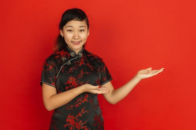 Жестикулируют, приглашают гостей. happy китайский новый год 2020. портрет азиатской молодой девушки на красном фоне. женская модель в традиционной одежде выглядит счастливой. праздник, человеческие эмоции. copyspace.