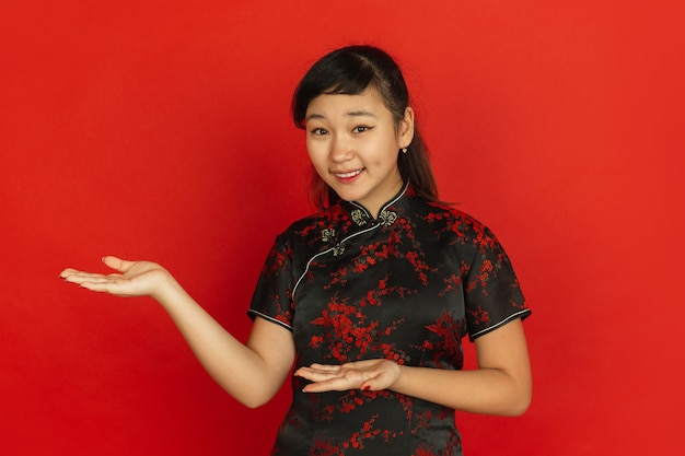 Gesturing, inviting guests. happy chinese new year 2020. asian young girl's portrait on red background. female model in traditional clothes looks happy. celebration, human emotions. copyspace.