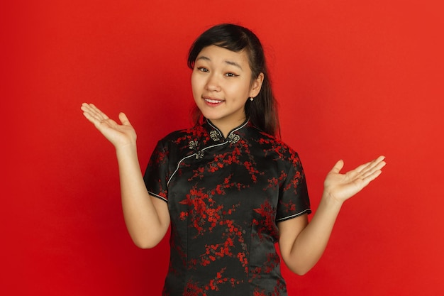 Gesturing, inviting guests. happy chinese new year. asian young girl's portrait on red background. female model in traditional clothes looks happy. celebration, human emotions. copyspace.
