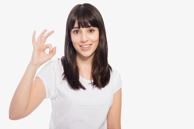 Очаровательная женщина gesturing ok