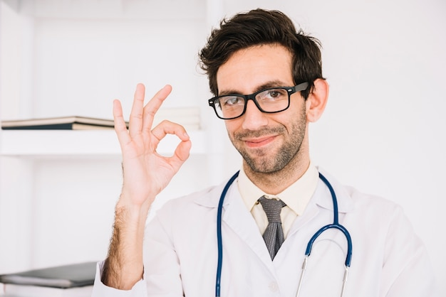 Счастливый мужской врач gesturing okay знак