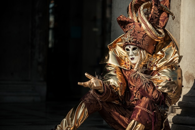 Gesturing person in venetian carnival costume of harlequin