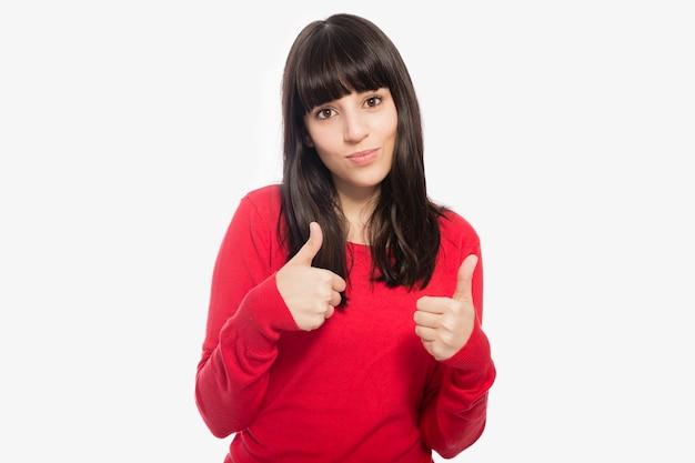 Симпатичная женщина gesturing thumb-up