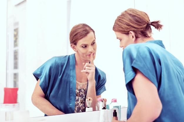 Жесты самому себе. сияющий злобный гендер-квир кокетливо позирует на фоне покрытого женскими тканями зеркала.