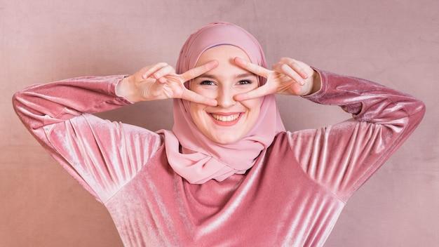 Взволнованная молодая женщина, gesturing v знак возле глаз, глядя на камеру