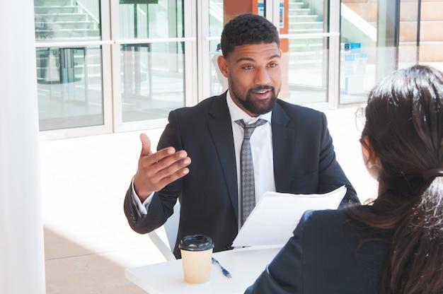 Бизнесмен, gesturing и разговаривать с партнером в кафе на открытом воздухе