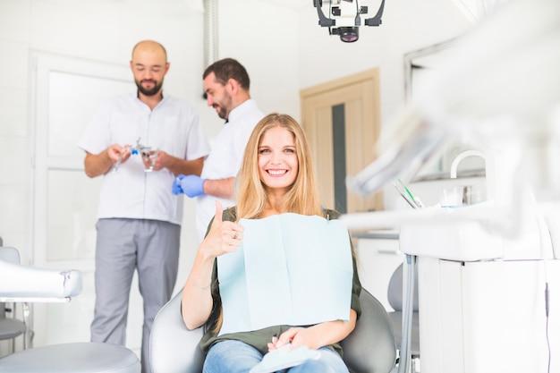 Улыбаясь женского пациента gesturing ок знак перед двумя мужчинами стоматолога