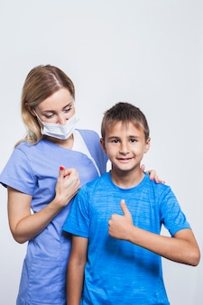Молодая женщина-стоматолог и мальчик gesturing палец вверх на белом фоне