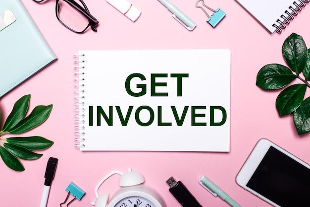 Get involvedは、ビジネスアクセサリーと緑の葉に囲まれたピンクの表面に白いノートに書かれています