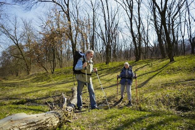 Собери новые вершины вместе. возрасте семейная пара мужчина и женщина в туристическом снаряжении, идущем на зеленой лужайке в солнечный день рядом с ручьем. концепция туризма, здорового образа жизни, релаксации и единения.