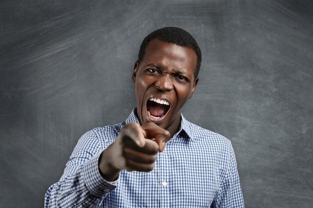 クラスから抜け出す!怒っている猛烈な若い黒肌の先生のヘッドショット。叫んで彼の不従順な生徒を指さし、彼の不正行為に怒り、彼を怒鳴りつけて叱責します。
