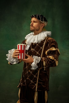 Get ready for cinema. portrait of medieval young man in vintage clothing standing on dark background. male model as a duke, prince, royal person. concept of comparison of eras, modern, fashion.