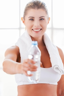 リフレッシュしましょう!水でボトルを伸ばして笑顔のスポーツ服の美しい成熟した女性