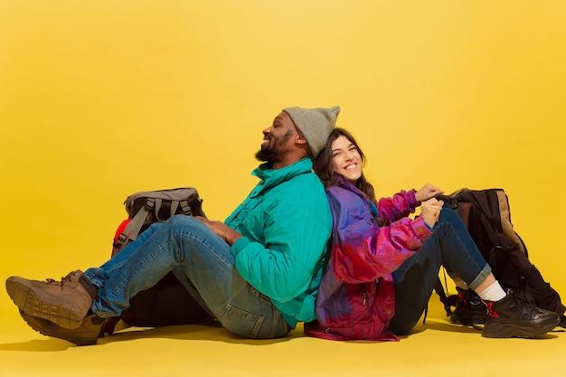 이 방법으로 함께하십시오. 노란색 스튜디오 배경에 고립 된 가방과 쾌활 한 젊은 관광객 부부의 초상화.