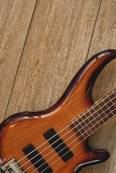악기에 대해 알아보세요. 나무 바닥에 금속 끈이 달린 일렉트릭 기타 본체의 보기를 닫습니다. 음악 개념입니다. 음악 장비. 악기.