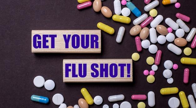 «получи свой грипп» написано на деревянных блоках возле разноцветных таблеток. медицинская концепция