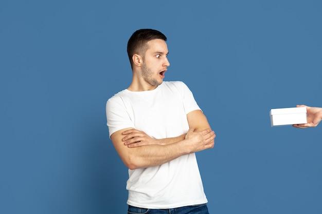 ギフトボックスを取得します。青い背景に白人の若い男の肖像画。