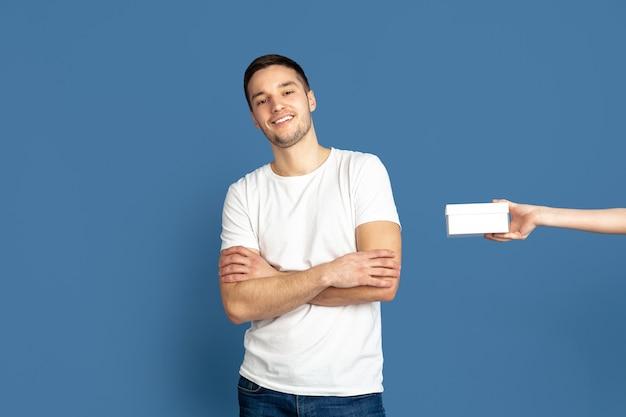 Получение подарочной коробки. портрет кавказского молодого человека на голубой стене студии.