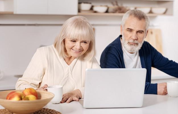 Знакомство с современными гаджетами. приятная улыбка с участием пожилой пары, сидящей дома и использующей ноутбук, выражая интерес и радость