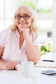 재정을 바로 잡습니다. 테이블에 앉아 있는 동안 턱에 손을 잡고 카메라를 보며 웃고 있는 행복한 노년 여성