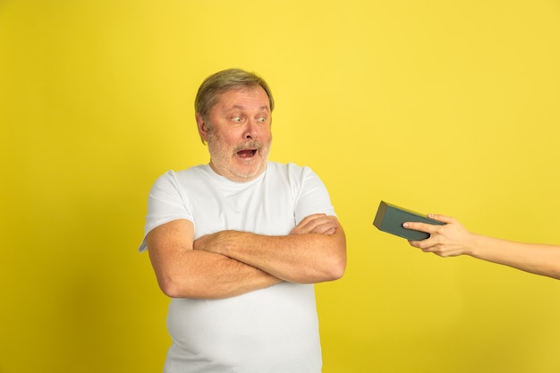 Getting a gift exciting. caucasian man portrait isolated on yellow studio background. beautiful male model in white shirt posing. concept of human emotions, facial expression, sales, ad. copyspace.