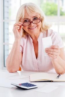 그녀의 재정을 바로 잡기. 테이블에 앉아 있는 동안 법안을 들고 카메라를 보며 웃고 있는 행복한 노년 여성