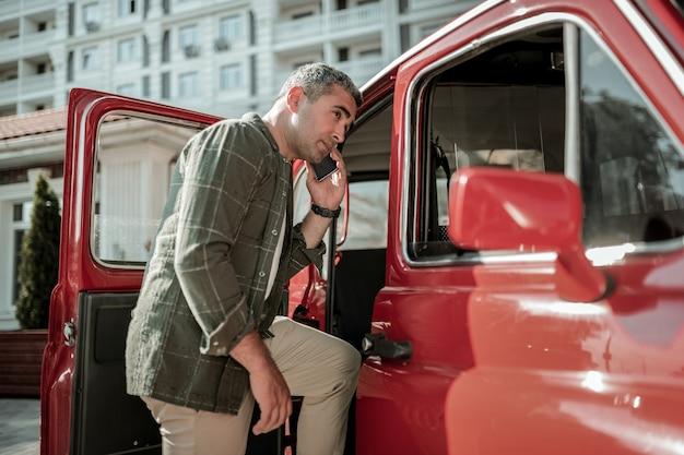 차에 타기. 문이 열린 차 근처에 서서 전화 통화를 하는 진지한 남자.