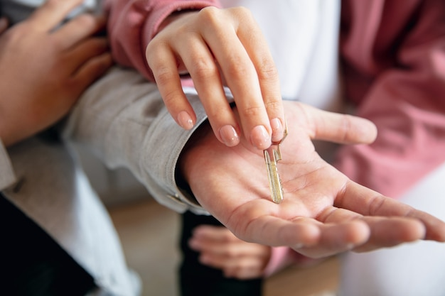 新しい家から鍵を入手する。新しい不動産所有者、新しい家、アパートに引っ越す若いカップル、手のクローズアップ。夢、愛、関係、不動産、インテリアコンセプト。一緒に新しい生活。