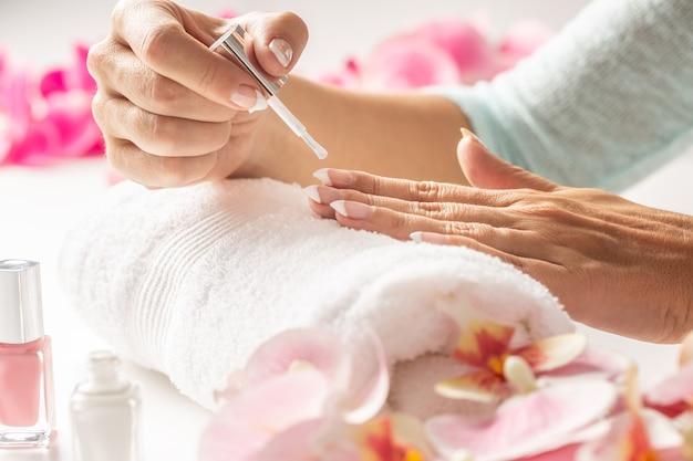 Делает маникюр женщиной, наносящей косметический лак для ногтей.