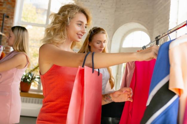 Получение нового платья. одежда, магазин одежды во время распродаж, летняя или осенняя коллекция. молодые женщины ищут новую одежду. понятие моды, стиля, предложений, эмоций, продаж, покупок. совершенно новые покупки.