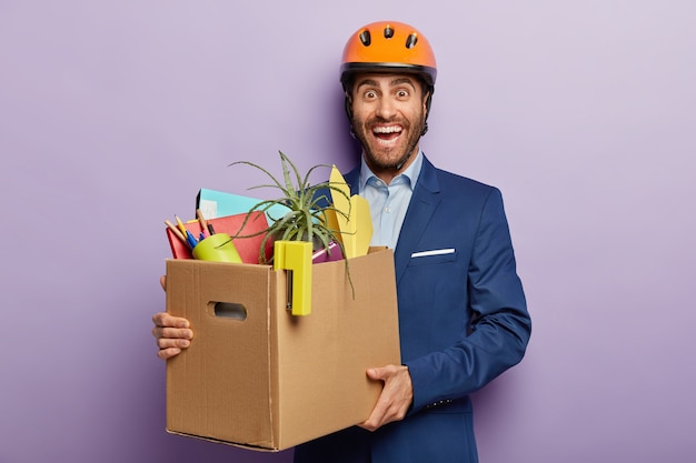Getting new job. happy caucasian architect in protective hardhat, wears formal suit, holds carton box with office stuff, moves in new cabinet isolated over purple wall rejoices first day at work