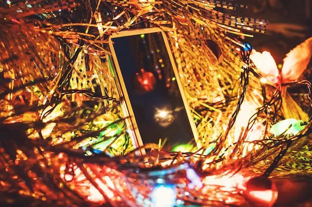 クリスマスプレゼントのオンライン配達を取得します。クリスマスの装飾が施されたテーブルの上のスマートフォン、輝くクリスマスライトの白い電話。コピースペース