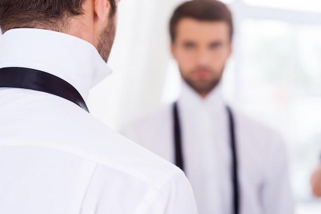 Готовимся к особому дню. вид сзади молодого человека в белой рубашке и развязанном галстуке, стоящего перед зеркалом