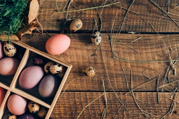 부활절을 준비합니다. 나무 상자에 있는 부활절 달걀과 건초가 있는 소박한 나무 테이블에 누워 있는 식물의 상위 뷰