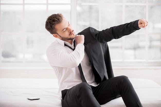 새로운 근무일을 위한 준비. 침대에 앉아있는 동안 재킷을 차려입고 있는 젊은 수염 남자