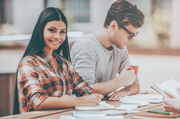 다음 수업을 준비합니다. 야외 나무 책상에 친구들과 앉아 메모장에 글을 쓰고 카메라를 바라보며 웃고 있는 젊은 여성