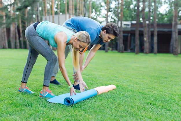 Готовимся к тренировке. позитивные молодые люди кладут коврики для йоги на траву, готовясь к тренировке