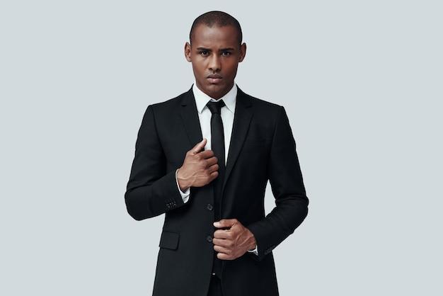 준비 중입니다. 회색 배경에 서있는 동안 카메라를 찾고 formalwear에서 잘 생긴 젊은 아프리카 남자