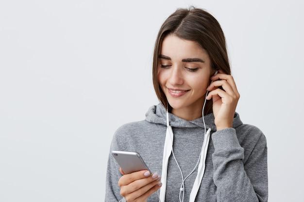 Prepararsi per la corsa mattutina. stile di vita urbano. ritratto di giovane bella ragazza caucasica con i capelli scuri in felpa con cappuccio sportiva grigia, indossando le cuffie, cercando playlist preferita su smartphone.