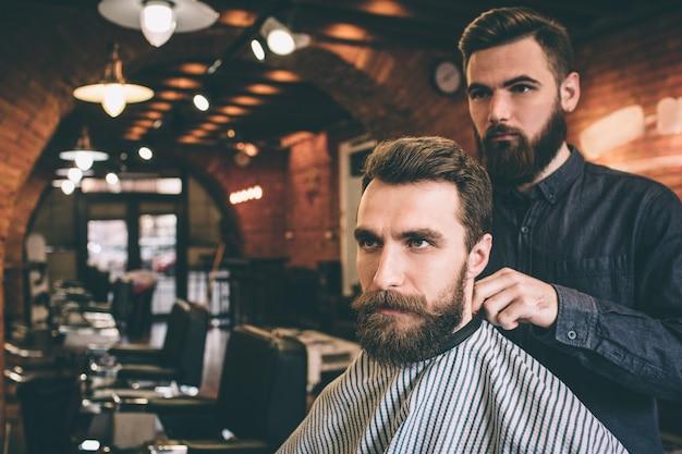 あごひげを切る準備をします。男は肩を覆われた椅子に座って、ひげを切る準備をしています。