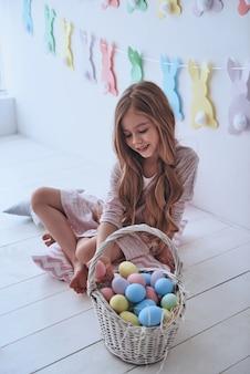 부활절을 준비합니다. 부활절 달걀을 들고 배경에 장식이 있는 베개에 앉아 웃고 있는 사랑스러운 소녀